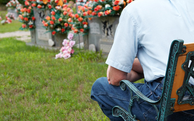 A man sitting beside a grave with focus on the man